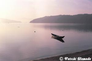 朝もやに小舟が浮かぶ入り江